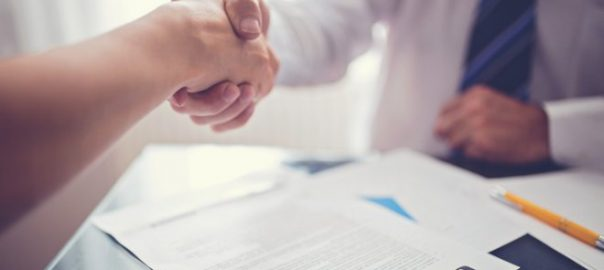 Two hands ,hand shaking,above contract paper